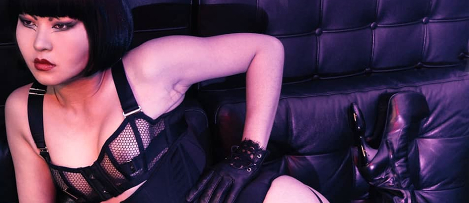 Dominatrix wears leather lingerie and high heeled boots